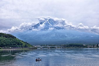 Person riding on boat on lake near mountain under white clouds during daytime
