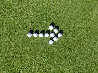 White golf balls forming arrow on green grass