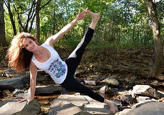Woman wearing white tank top Stretching legs  on top of gray rock