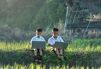 Two boys in white dress shirt sitting on grass using laptop computers