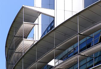 Glass wall building under clear blue sky during daytime