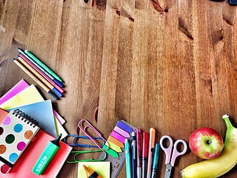 Assorted color pencils and scissors on brown wooden table