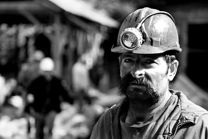 Grayscale photography of man wearing hard helmet