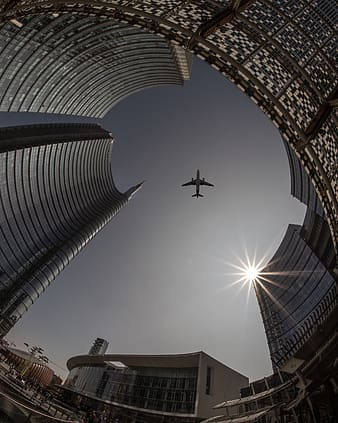 Airplane flying over the building during daytime