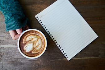 Person holding white mug with coffee beside notebook