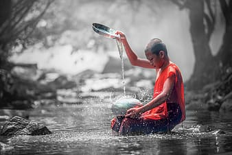 Selective color photography of Buddhist monk in orange orange robe
