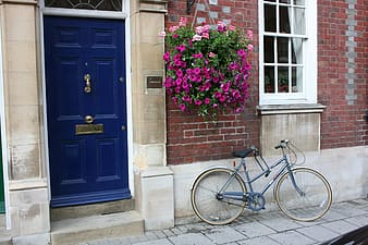 Bicycle parked next to house with blue door ]