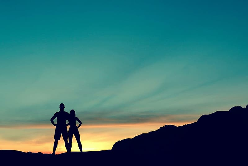 Silhouette of 2 men standing on rock formation during sunset