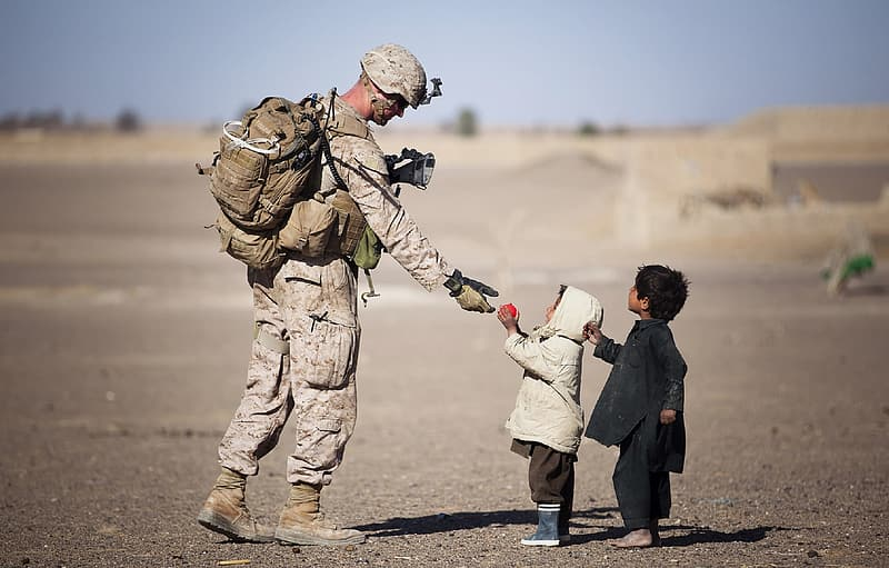 Child giving a pink ball to a marine soldier