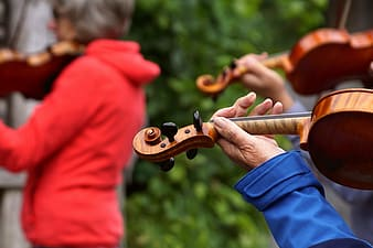 Person in red long sleeve shirt playing violin during daytime