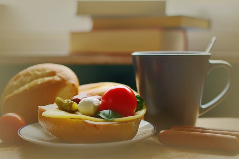 Baked bread placed on white ceramic saucer near black ceramic mug placed on brown wooden table