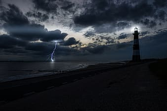 White and black lighthouse near sea under cloudy sky during daytime