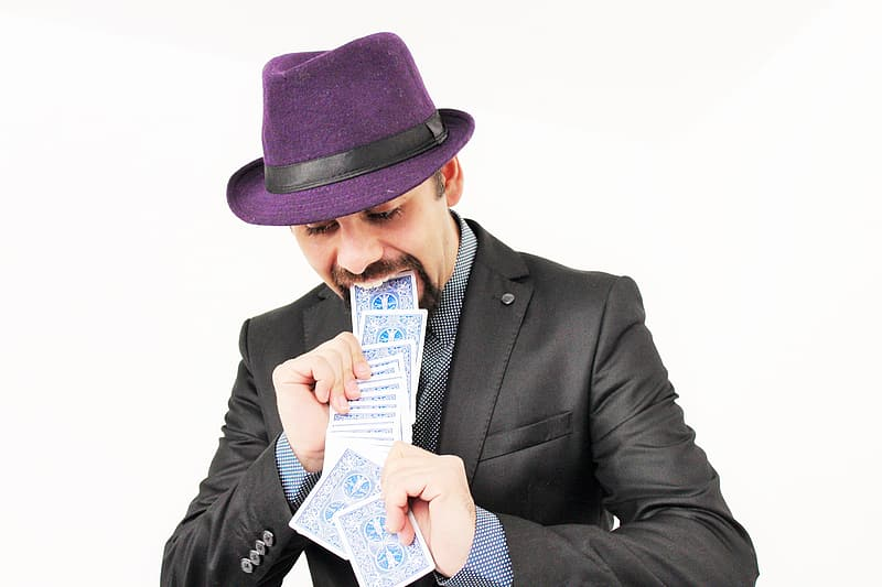 Man in black suit holding blue and white card