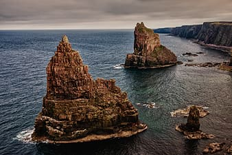 Two brown rock formations in sea near cliffs