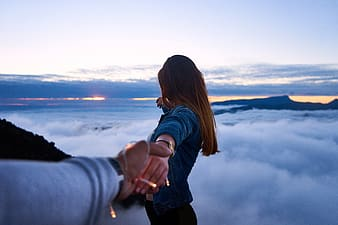 Man holding woman's hand on top of mountain