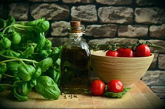 Cherry tomatoes, green spinach and olive oil sitting on the table