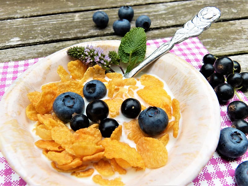 Corn flakes with black berries and cream on plate placed on table