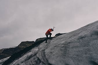 Man holding pickaxe on gray rock