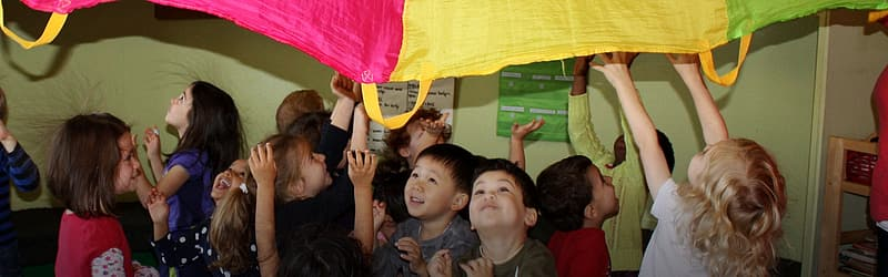 Group of children holding yellow and green flag
