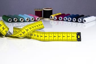 Yellow measuring tape beside blue and red plastic tape