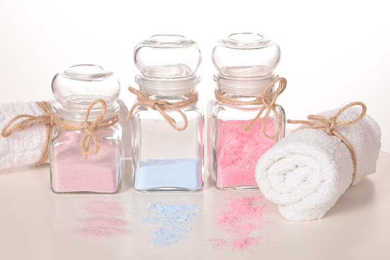 White towel beside three clear glass bottles with powders on brown surface