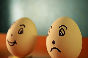 Two white eggs with happy and sad emotion print