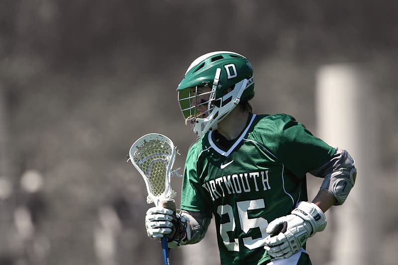 Selective focus photo of man holding lacrosse stick