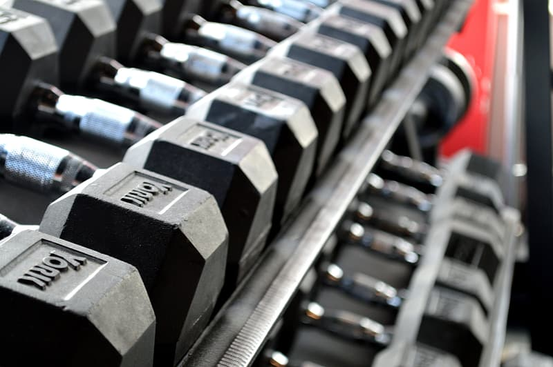 Gray-and-black dumbbell lot on gray metal rack