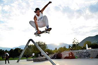 Man in white t-shirt and brown shorts riding skateboard during daytime