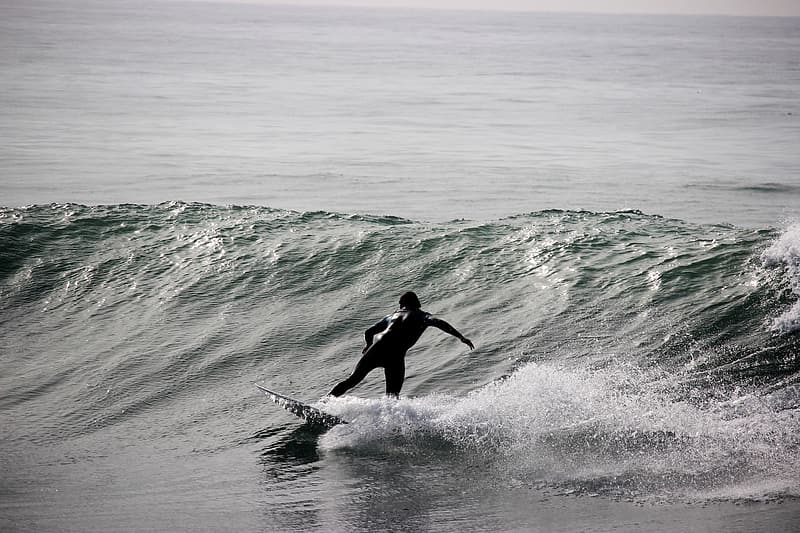 Grayscale photography of person riding surfboard on barrel waves