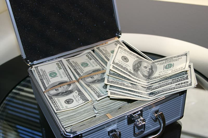 Bundle of 100 US dollar banknote with silver briefcase