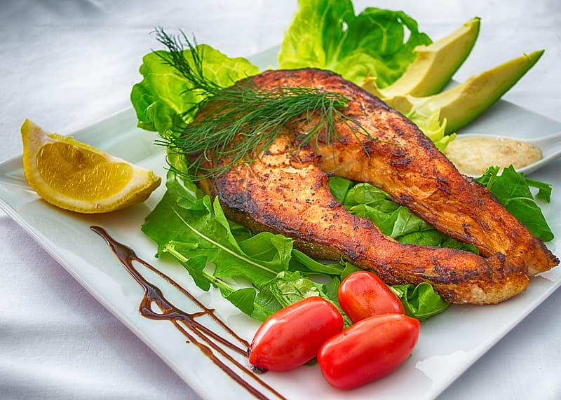 Cooked fish on plate with side dish