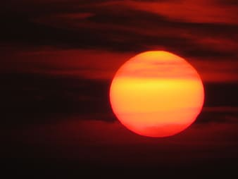 Red sun covered by clcouds