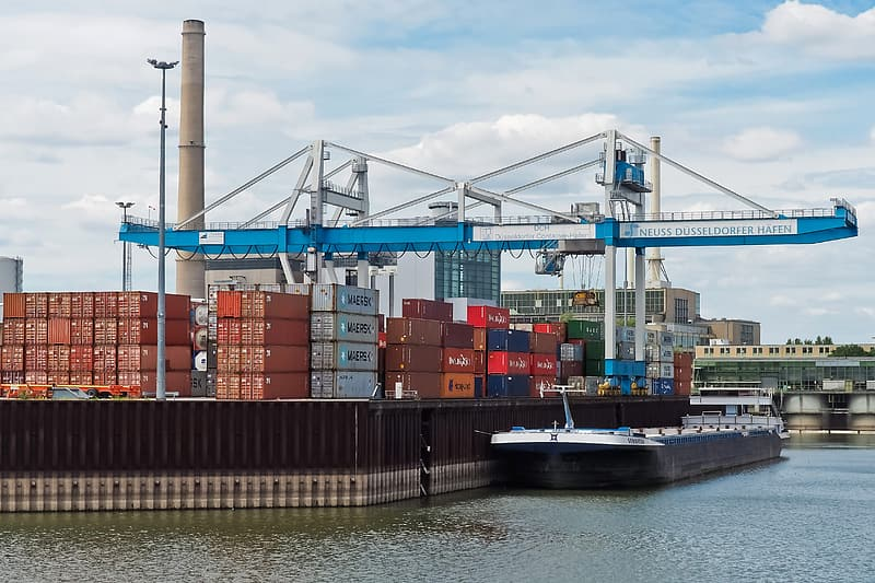 Blue and white intermodal container crane near shipping boat and port