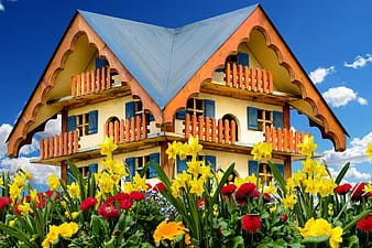 Beige and orange house surrounded by flowers