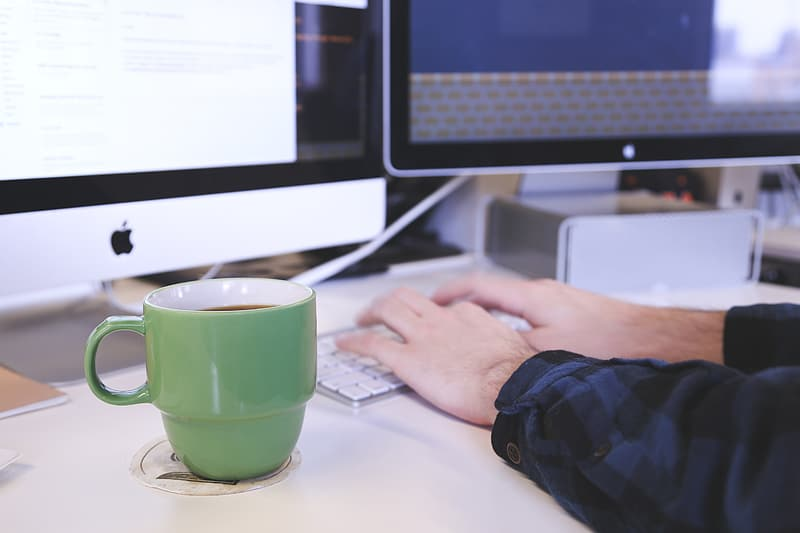 Green ceramic mug on top of white coaster near person hand holding Apple Keyboard