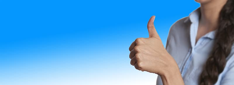 Woman wearing blue collared button-up showing thumbs up