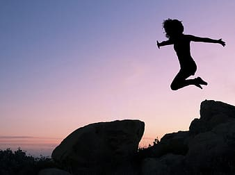 Silhouette of girl jumping in front of rock