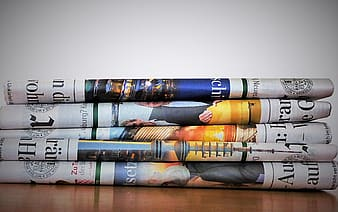 Several newspapers on top of brown wooden surface