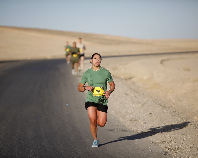 Selective focus photography of running woman wearing green shirt on road during daytime