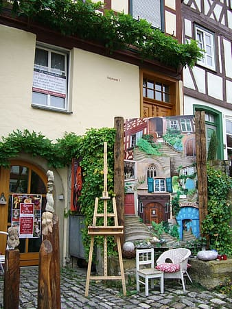 Brown easel stand beside painting in front of building