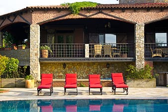 Four red loungers beside swimming pool
