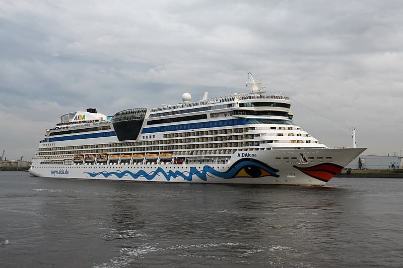 White and blue cruise ship on sea under cloudy sky during daytime