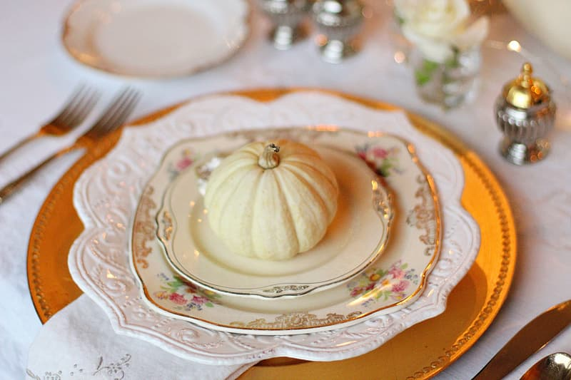 Small artificial squash on white ceramic saucer with plates