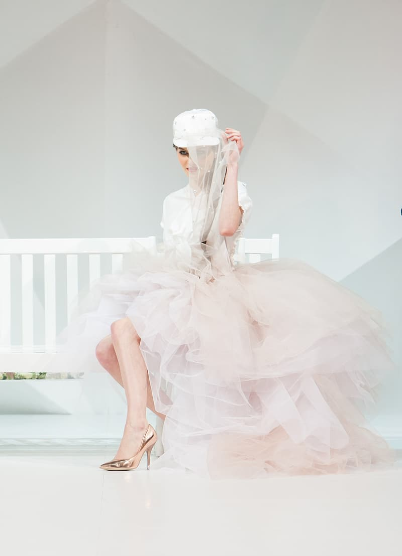 Woman in white and pink dress sits on white wooden bench