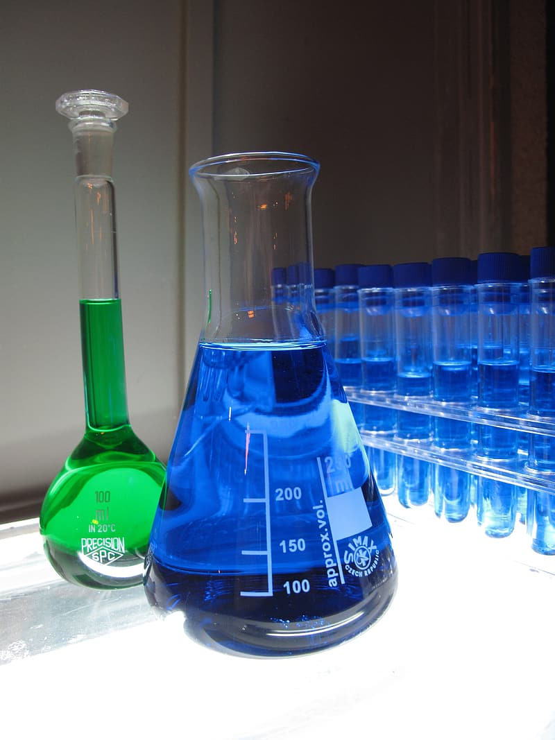 Two green and blue liquid filled clear glass containers