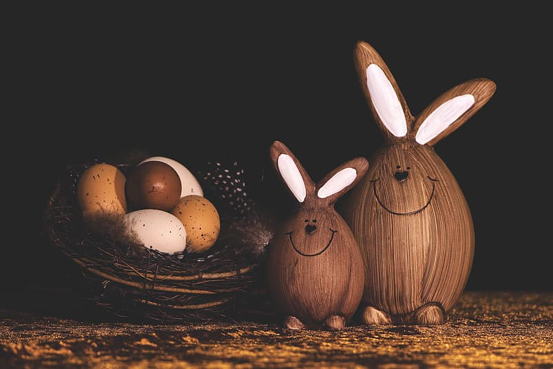 Two brown rabbit figurines on brown wooden table