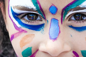 Close view of person's face with blue, teal, and white face paint