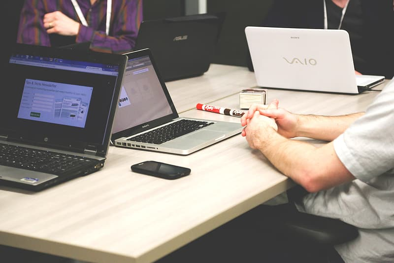 Person holding red pen near macbook pro