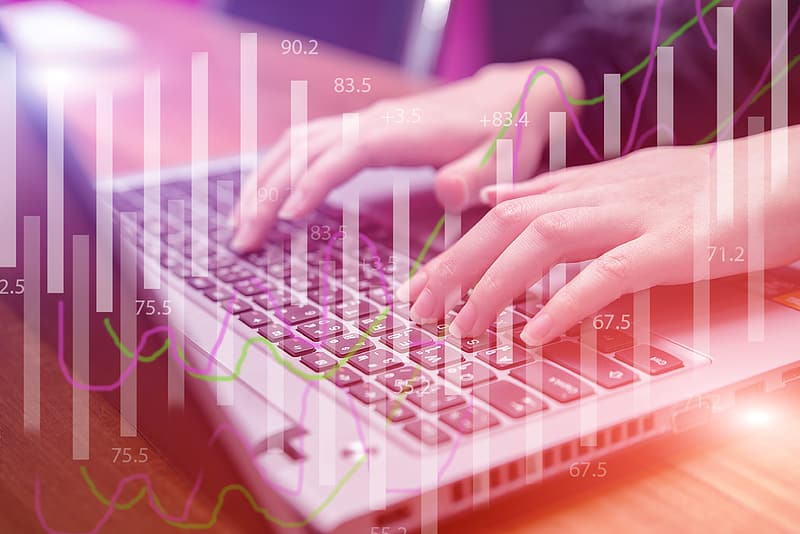 Person operating laptop with bar graph background